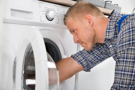 professional technician repairing a washer